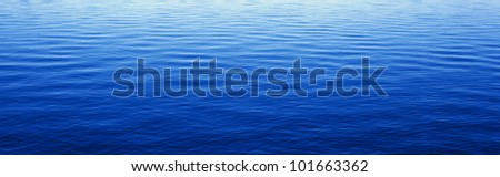 These are water reflections in Lake Tahoe. The water is a deep blue and the small ripples in the water form a pattern. - stock photo