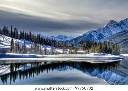 These cross reflections are on the south end of Old Goat Pond in Spray Valley Provincial Park in Alberta, Canada. - stock photo