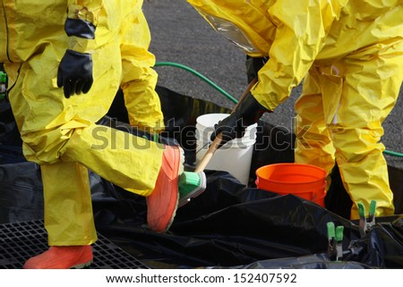 These HAZMAT team members have been wearing protective suits to protect them from hazardous materials during a disaster preparedness drill and have to go through decontamination washes. - stock photo