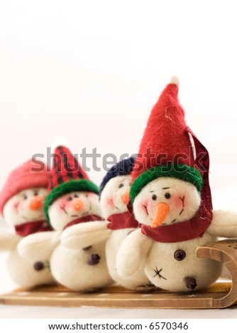 These snowmen are bundled up to go sledding.  Copy space across top.  Selective Focus on lead snowman. - stock photo