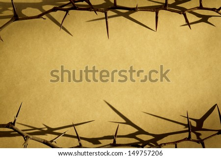 These Thorn Branches against a parchment paper background represent God's Suffering and Dying on the Cross on Good Friday and his Rising on Easter Sunday. - stock photo