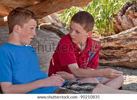 These two Caucasian brothers are talking in their makeshift fort they made at a beach.  One is 13 the other 11 year old boys, waist up, side view horizontal image of family together. - stock photo