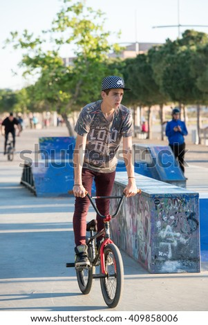 Thessaloniki, Greece - April 15, 2016: a cyclist young boy is riding his bike and doing stunts on a ramp in a park in Thessaloniki Greece  - stock photo