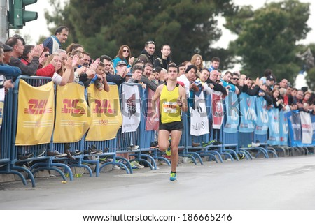 THESSALONIKI, GREECE - APRIL 6, 2014 :  Runner SYMIRIOTIS KYRIAKOS finishing proudly in the 9th Marathon Alexander the Great. The marathon is an annual event.  - stock photo