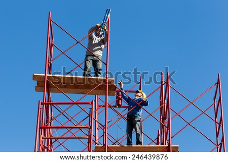THESSALONIKI, GREECE - JANUARY 15, 2015: Unidentified workers setting up iron scaffolding at construction area - stock photo
