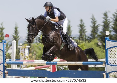 THESSALONIKI, GREECE, JUNE 14, 2015: Unknown rider on a horse during competition matches riding round obstacles