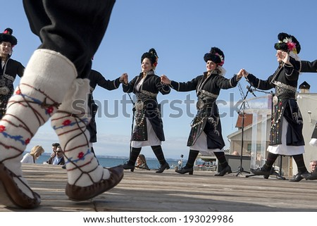 THESSALONIKI, GREECE, OCTOBER 2, 2013: Olympic flame holder ceremony. Group performing Greek folklore dance. - stock photo