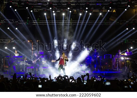 THESSALONIKI, GREECE, SEPTEMBER 11, 2014: Singer Sakis Rouvas performing at MAD North Stage festival by Thessaloniki International Fair. Blur stage spotlights with laser rays in the background.  - stock photo
