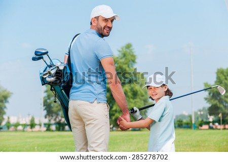 They are the big golf fans. Happy young man and his son holding hands and looking at camera while walking on the golf course - stock photo