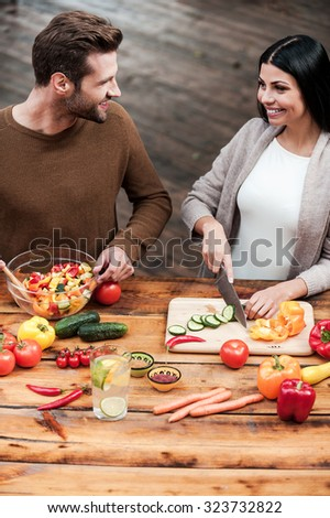 They love cooking together. Top view of beautiful young couple preparing food together and smiling - stock photo