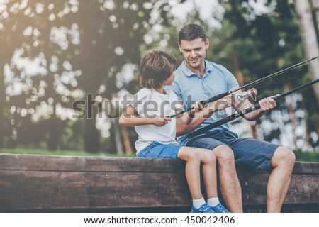 They love fishing together. Cheerful father and son fishing while sitting on quayside - stock photo