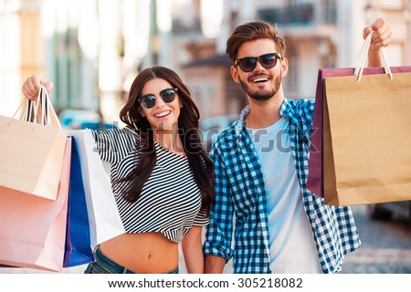 They love shopping together. Cheerful young loving couple stretching out shopping bags and smiling while walking along the street  - stock photo