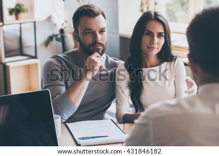 They need an expert advice. Confident young couple listening to some man sitting in front of them at the desk - stock photo