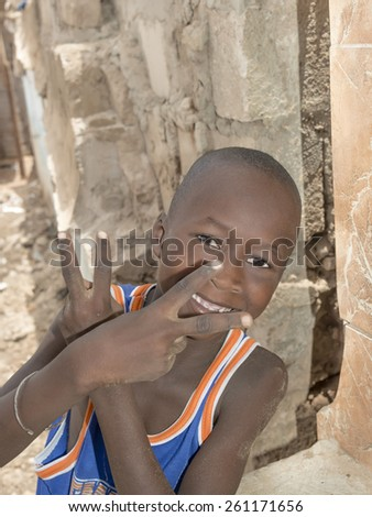 THIAROYE, SENEGAL - AUGUST 2, 2014: Unidentified boy playing in the street, popular district of Guinaw Rails - stock photo