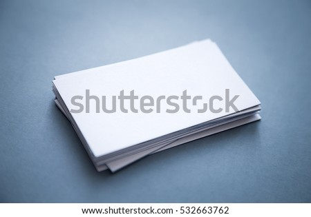 Thick blank business cards stacked up on a grey background with blurred front and back corners.
