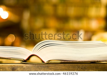 Thick book open in bookshop, bookshelves in the background - stock photo