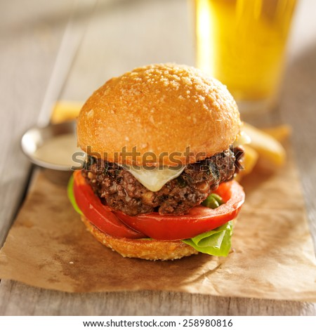 thick burger on brioche bun served with beer - stock photo