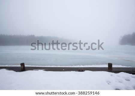 Thick fog at frozen lake landscape - stock photo