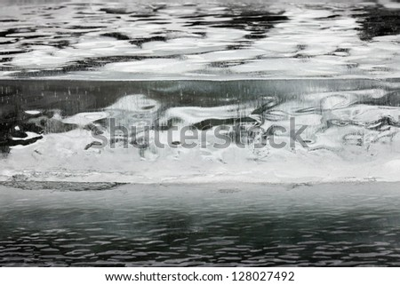 Thick layer of ice with straight crevasse crack and round trapped air bubbles background texture pattern - stock photo