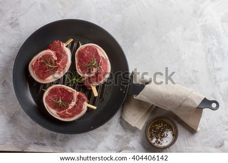 Thick raw beef with seasoning and rosemary on the grill pan, selective focus - stock photo