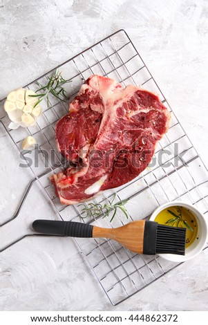 Thick raw T-bone steak with seasoning and rosemary for grill, selective focus - stock photo