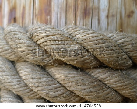 Thick rope around a dock piling keeping a lobster boat docked