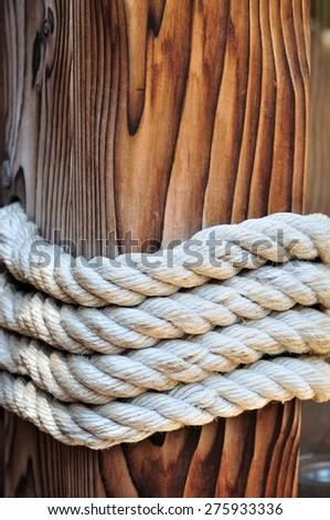 Thick rope around a wooden mooring bollard keeping a boat docked. Croatia - stock photo