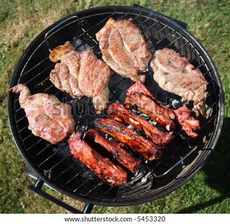 thick seasoned pork chops and chinese style lamb ribs cooking on the bbq grill - stock photo