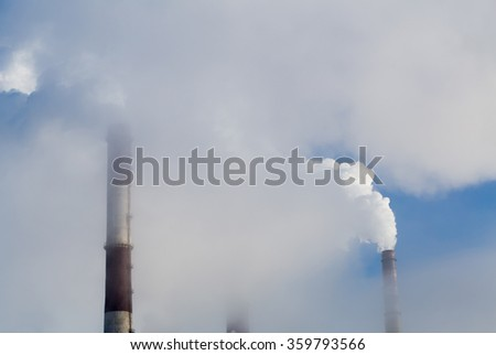 Thick smoke in the sky. Power plant pipes smoking in the sky