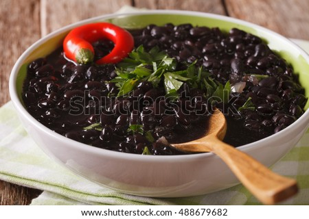 thick soup of black bean with chilli peppers close up in a bowl on the table. horizontal