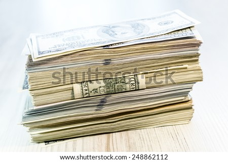 Thick stack of US cash located at some angle. The stack of US cash in mixed notes of different colors and tones on the wooden table - stock photo