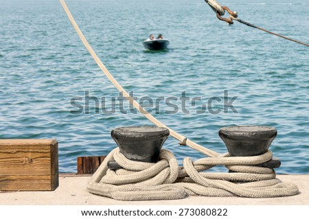 Thick strong boat rope tied to heavy steel docking cleats. Blue water and people motor boating in blurred background.  - stock photo