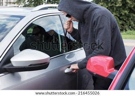 Thief breaking car door lock - stock photo