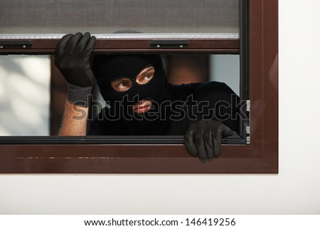Thief Burglar opening window during house breaking - stock photo