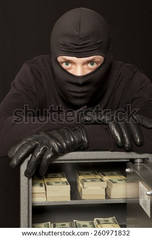 Thief burglar stealing dollar money during home safe code breaking - stock photo