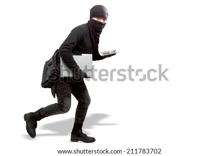 thief dressed in black and wearing a balaclava stealing a laptop computer in concept  cyber criminal committing Internet isolated on white background with clipping path - stock photo