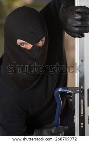 Thief entering a private home to steal - stock photo