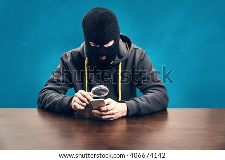 Thief hacking mobile phone information security concept - stock photo