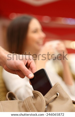 Thief hand stealing a mobile phone from a woman bag while she is relaxed - stock photo