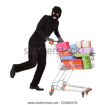Thief in a black costume and balaclava pushing a shopping trolley full of gifts and presents from a celebration isolated on white - stock photo