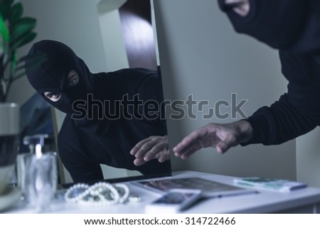 Thief in balaclava breaking into the house - stock photo