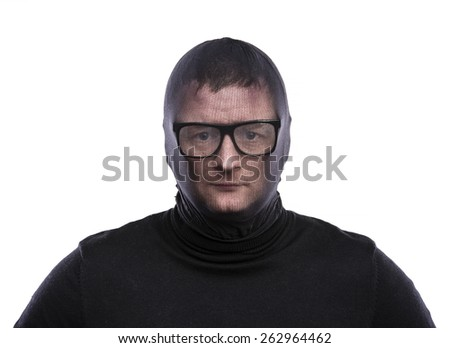 Thief in balaclava making funny faces, dressed in black. Studio shot on white background.