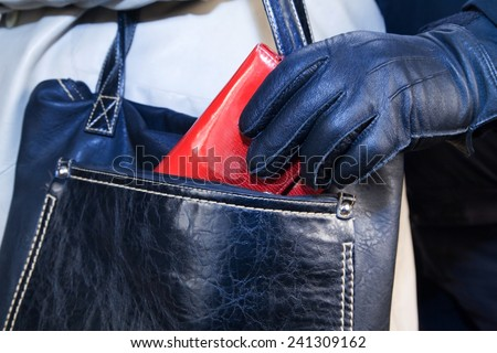 Thief in gloves stealing a purse  from the women's bags - stock photo