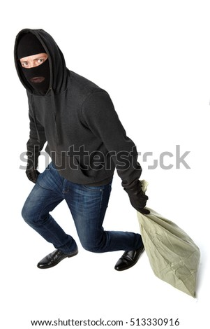 Thief in mask carries bag