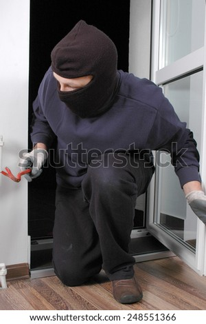 Thief in the balaclava and with crowbar in the hand at home