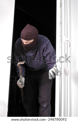 Thief in the balaclava and with crowbar in the hand at home - stock photo