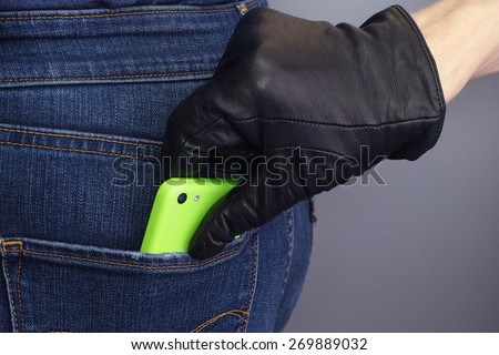 Thief is stealing mobile phone from back pocket of a woman.  - stock photo