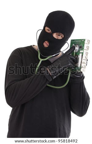 Thief listening to a computer chip with a stethoscope - stock photo