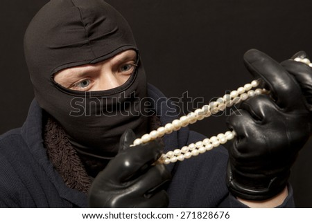 Thief. Man in black mask with a pearl necklace. Focus on thief - stock photo