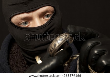 Thief. Man in black mask with a silver bracelet. Focus on thief - stock photo